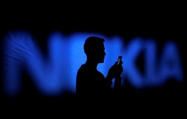 A photo illustration of a man silhouetted against a Nokia logo in the central Bosnian town of Zenica January 23, 2014.      REUTERS/Dado Ruvic/File Photo