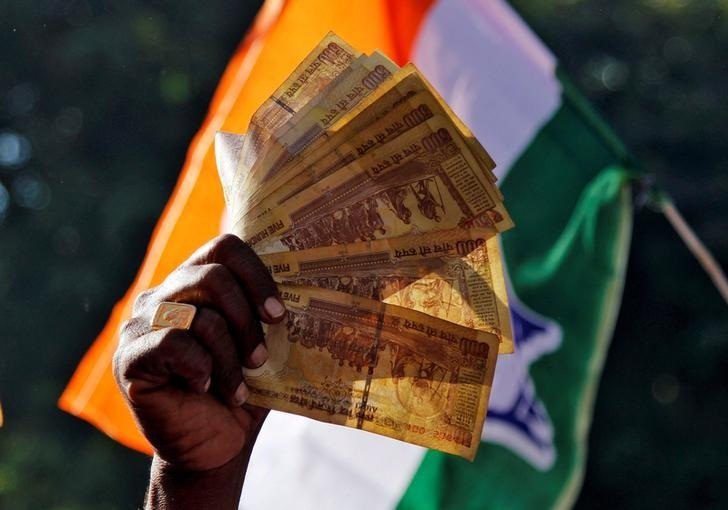 FILE PHOTO - A man displays 500 Indian rupee notes during a rally organised by India's main opposition Congress party against the government's decision to withdraw 500 and 1000 Indian rupee banknotes from circulation, in Ajmer, India, November 24, 2016. REUTERS/Himanshu Sharma/File Photo
