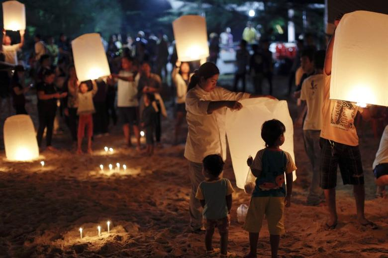 Survivors, local residents and visitors release paper lanterns during the ceremony for victims of the 2004 tsunami in Ban Nam Khem, a fishing village destroyed by the wave December 26, 2014. REUTERS/Athit Perawongmetha