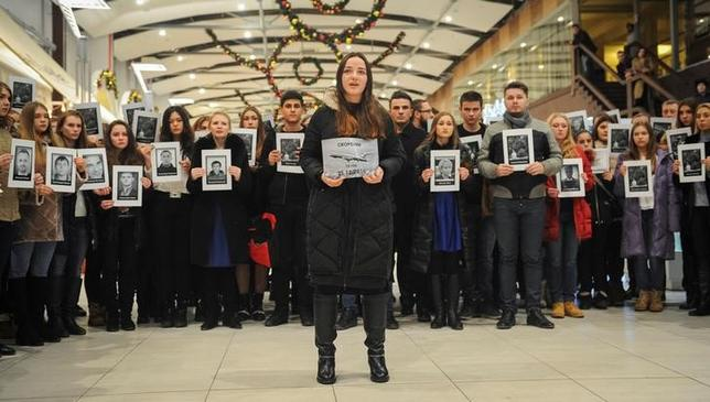 People hold portraits and printed names of victims of the Tu-154 plane, which crashed into the Black Sea on its way to Syria on Sunday, during a memorial event in Rostov-On-Don, Russia December 26, 2016. REUTERS/Sergey Pivovarov