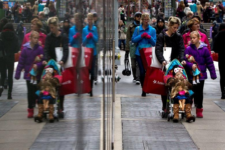 Shoppers are reflected in a window as they walk though Times Square in New York November 30, 2014.   REUTERS/Carlo Allegri