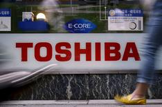 Pedestrians walk past a logo of Toshiba Corp outside an electronics retailer in Tokyo, Japan, June 25, 2015. REUTERS/Yuya Shino/File Photo