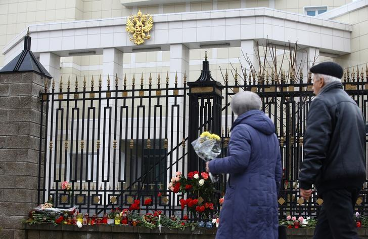 People place flowers to commemorate passengers and crew members of Russian military plane, which crashed into the Black Sea on its way to Syria on Sunday, at the Russian embassy in Minsk, Belarus December 26, 2016.  REUTERS/Vasily Fedosenko