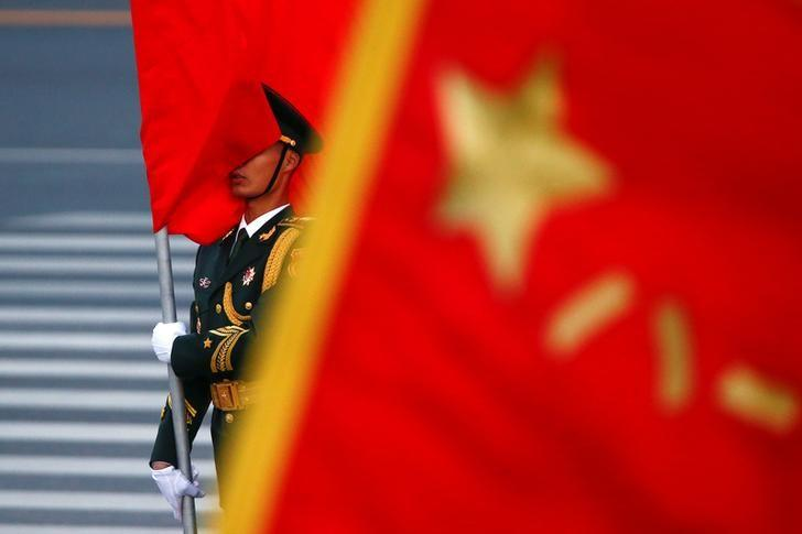 A red flag is wrapped around the face of an honour guard soldier as Chinese Premier Li Keqiang and Belgian Prime Minister Charles Michel attend a welcoming ceremony at the Great Hall of People in Beijing, China, October 31, 2016. REUTERS/Thomas Peter/Files