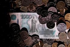 Рублевые монеты и банкноты. Рубль к доллару в течение торговой сессии пятницы продолжает снижаться перед длительным перерывом в работе биржи, когда большинство игроков уже ушли с рынка, а спрос на подешевевшую до приемлемых уровней валюту упирается в отсутствие достаточного предложения. REUTERS/Maxim Zmeyev/Illustration