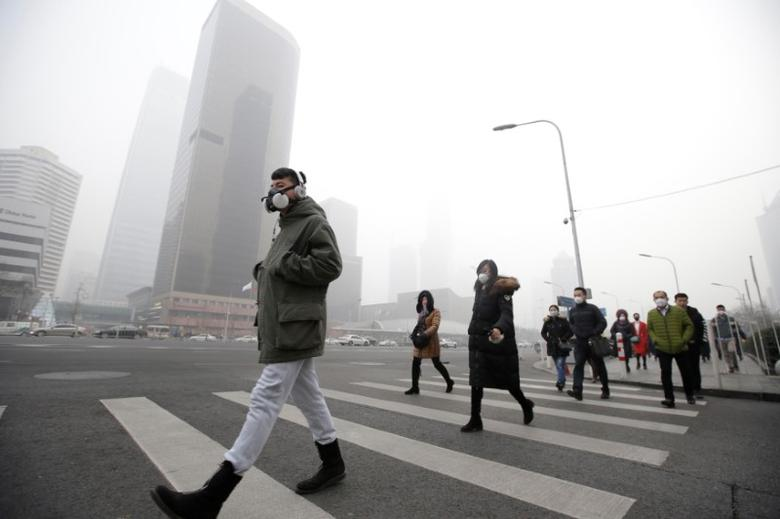A man wearing a respiratory protection mask walks toward an office building during the smog after a red alert was issued for heavy air pollution in Beijing's central business district, China, December 21, 2016. REUTERS/Jason Lee