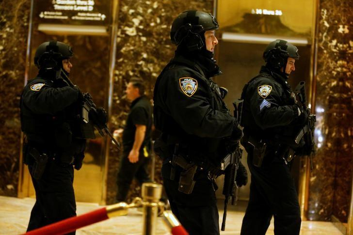 New York City Police officers assigned to protect U.S. President-elect Donald Trump walk through the lobby of Trump Tower in New York, U.S. January 2, 2017. REUTERS/Jonathan Ernst