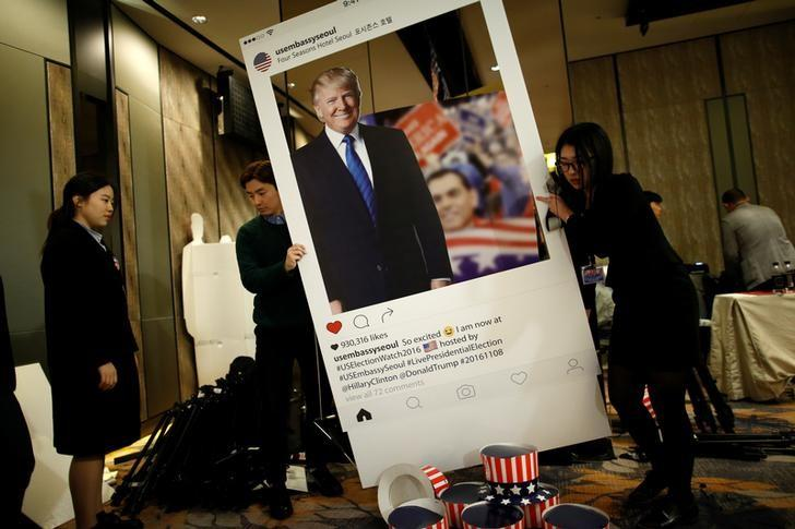 Officials move a sign of Republican U.S. presidential nominee Donald Trump after a U.S. Election Watch event hosted by the U.S. Embassy at a hotel in Seoul, South Korea, November 9, 2016.   REUTERS/Kim Hong-Ji/Files