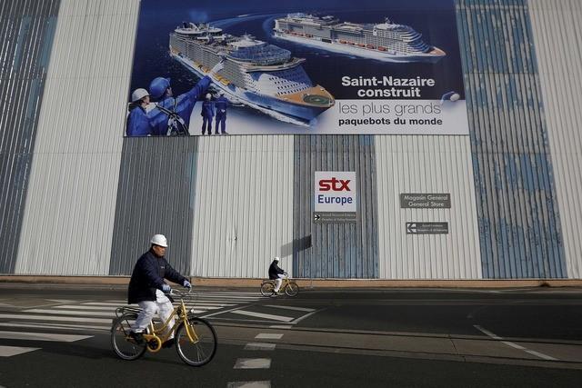 FILE PHOTO Shipbuilders ride past a giant poster November 9, 2016 at the STX Les Chantiers de l'Atlantique shipyard site in Saint-Nazaire, western France. REUTERS/Stephane Mahe/File Photo