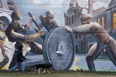 """Una persona paseando a un perro frente al mural sobre obreros """"Visual Interpretations of Pullman"""", en el barrio Pullman de Chicago, EEUU, nov 20, 2014. La actividad fabril en Estados Unidos se aceleró a un máximo nivel en dos años en diciembre, ante una fuerte alza de nuevos pedidos y del empleo, lo que sugiere que parte del lastre sobre las manufacturas vinculado al petróleo se estaba disipando.       REUTERS/Andrew Nelles/File Photo"""
