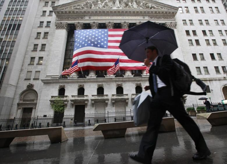 Morning commuters walk pass the New York Stock Exchange in the rain, June 4, 2012.  REUTERS/Brendan McDermid
