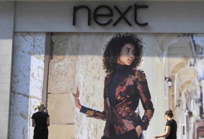 Shoppers pass a branch of Next retail in London, Britain, September 15, 2016.    REUTERS/Toby Melville/File Photo