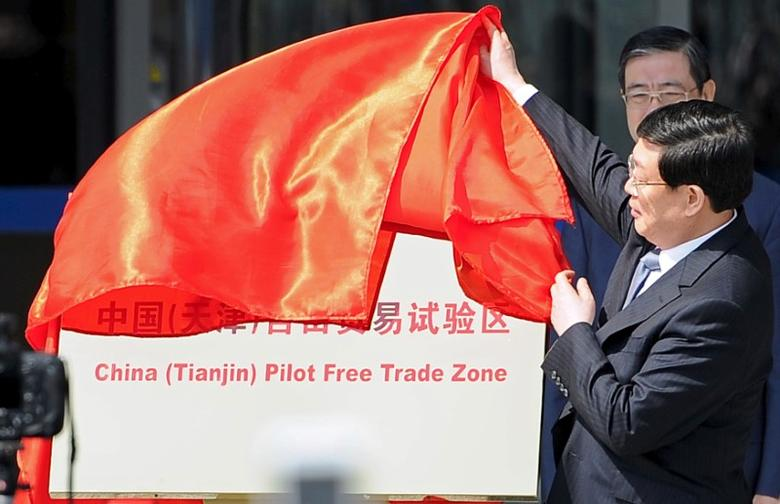 Tianjin municipal Mayor Huang Xingguo removes the veil covering a sign reading ''China (Tianjin) Pilot Free Trade Zone'', at an unveiling ceremony in Tianjin municipality, April 21, 2015. REUTERS/Stringer/File Photo