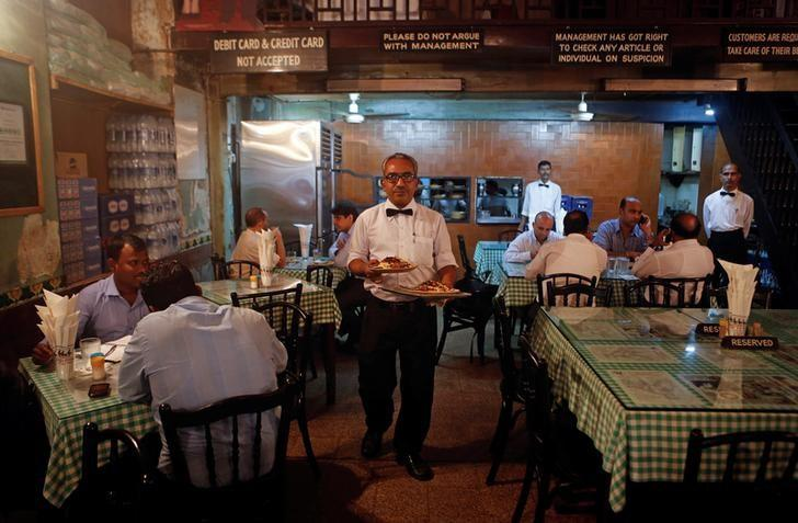 A waiter carries plates of food for customers at the Britannia and Co. restaurant in Mumbai September 19, 2013.   REUTERS/Danish Siddiqui/File Photo