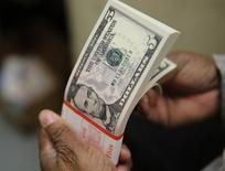 Um pacote de notas de cinco dólares, estampadas com o rosto do ex-presidente Abraham Lincoln, é inspecionada em Washington, nos Estados Unidos 26/03/2015 REUTERS/Gary Cameron/File Photo