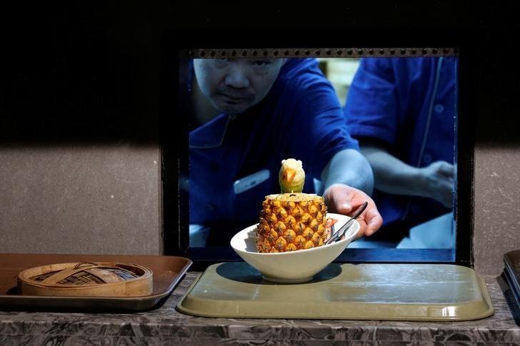 A cook delivers a fried rice with pineapple from the kitchen at Dim Sum Icon restaurant in Hong Kong, China July 25, 2016. Picture taken July 25, 2016.   REUTERS/Bobby Yip