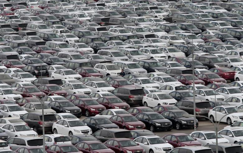An employee yawns as he walks among General Motors' new Chinese-made cars at a parking lot in Shenyang, Liaoning province April 21, 2014. REUTERS/Stringer