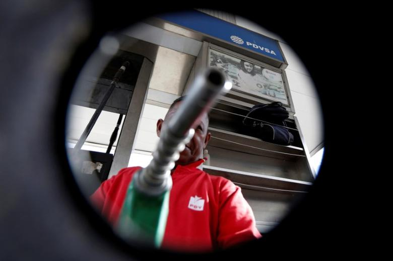FILE PHOTO:  A man points a fuel nozzle at the camera for a photograph at a gas station belonging to Venezuelan state oil company PDVSA in Caracas, Venezuela, July 21, 2016.   REUTERS/Carlos Jasso/File Photo