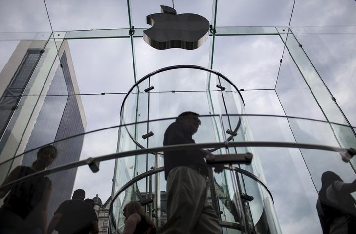 Customers enter the Apple store on 5th Avenue beneath an Apple logo in the Manhattan borough of New York City, July 21, 2015. REUTERS/Mike Segar/File Photo