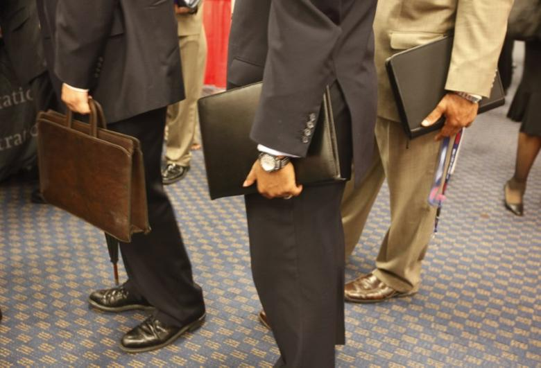 Attendees at a job fair line up for an interview carrying their resumes in leather bags in a Washington hotel, August 6, 2009. REUTERS/Jason Reed