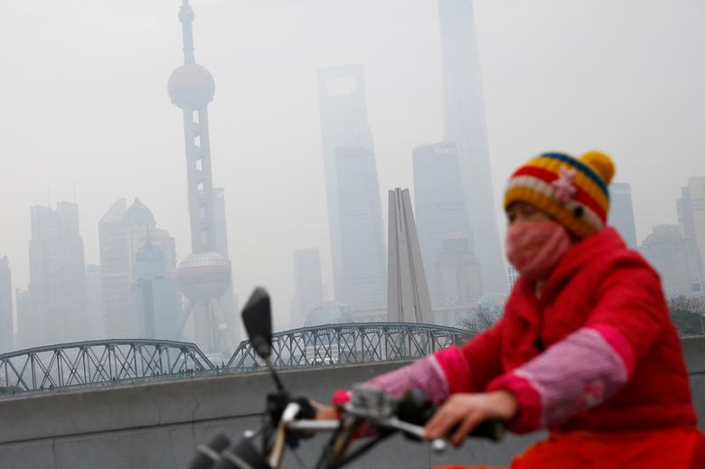A woman wears a mask as she rides near the Bund during a polluted day in Shanghai, China, January 2, 2017.  REUTERS/Aly Song