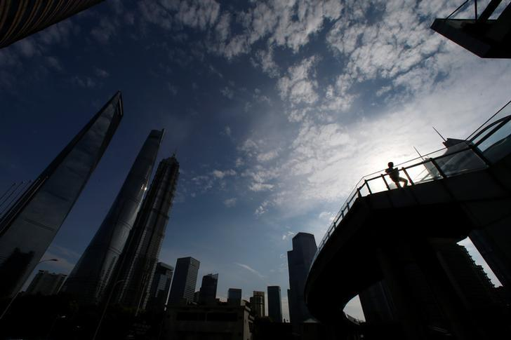 A man walks on a bridge in the financial district of Pudong in Shanghai, China June 22, 2016. REUTERS/Aly Song - RTX2HJIA