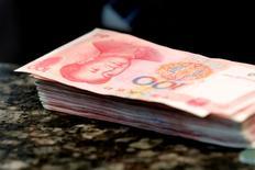 Le yuan reste relativement stable face au dollar lundi malgré la décision de la banque centrale chinoise d'abaisser le taux de référence de la devise, après une semaine extrêmement volatile qui a vu le yuan s'apprécier de 1% avant de retomber. /Photo d'archives/REUTERS/Kim Kyung-Hoon