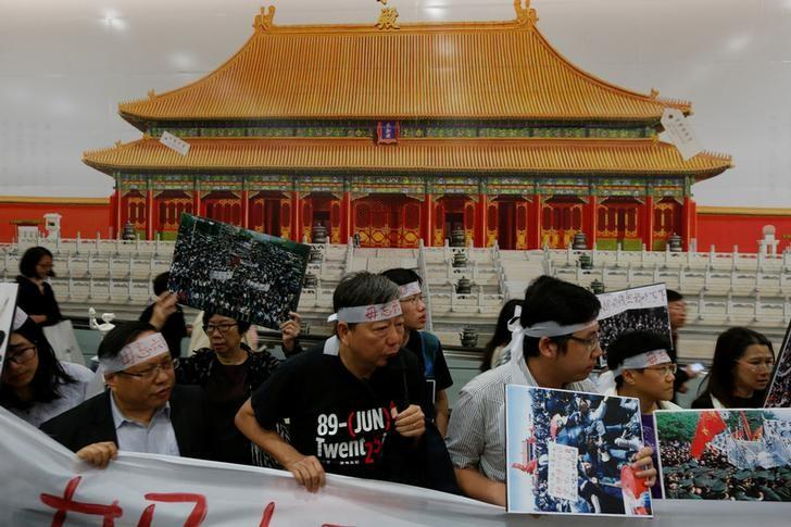 Pro-democracy activists protest in front of an illustration of Beijing's Palace Museum in Hong Kong, China, January 9, 2017. REUTERS/Bobby Yip