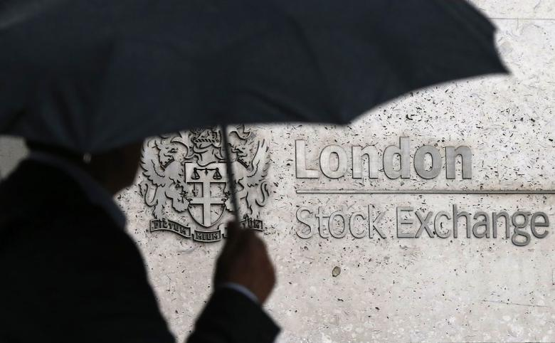 A man shelters under an umbrella as he walks past the London Stock Exchange in London, Britain August 24, 2015.  REUTERS/Suzanne Plunkett/Files