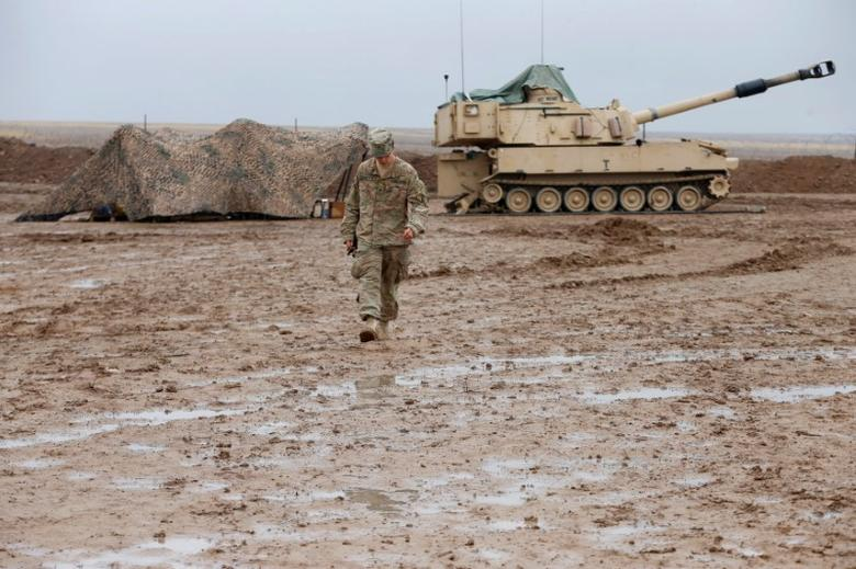A U.S. soldier walks in front of a tank at an army base in Karamless town, east of Mosul, Iraq, December 25, 2016. REUTERS/Ammar Awad