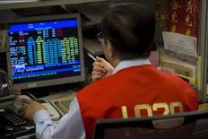 Un operador trabajando en la bolsa de Hong Kong, jul 8, 2015.Las bolsas de Asia subían el martes y los precios del petróleo languidecían cerca de mínimos de tres semanas, en medio de la incertidumbre de los inversores sobre si los recortes de bombeo por parte de algunos exportadores importantes serán suficientes para compensar el aumento de la oferta de otros productores.REUTERS/Tyrone Siu