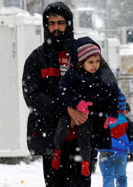 Stranded Syrian refugee carries his child through a snow storm at a refugee camp north of Athens, Greece January 10, 2017.REUTERS/Yannis Behrakis