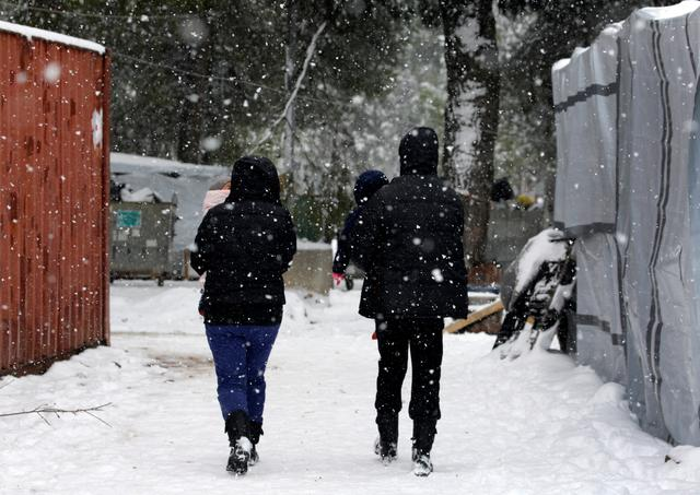 Stranded Syrian refugees carry their children through a snow storm at a refugee camp north of Athens, Greece January 10, 2017.REUTERS/Yannis Behrakis
