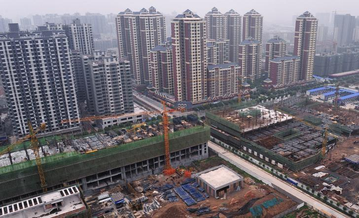 Newly constructed residential buildings (back) are seen next to a construction site in Xi'an, Shaanxi province May 25, 2012. REUTERS/Rooney Chen/Files