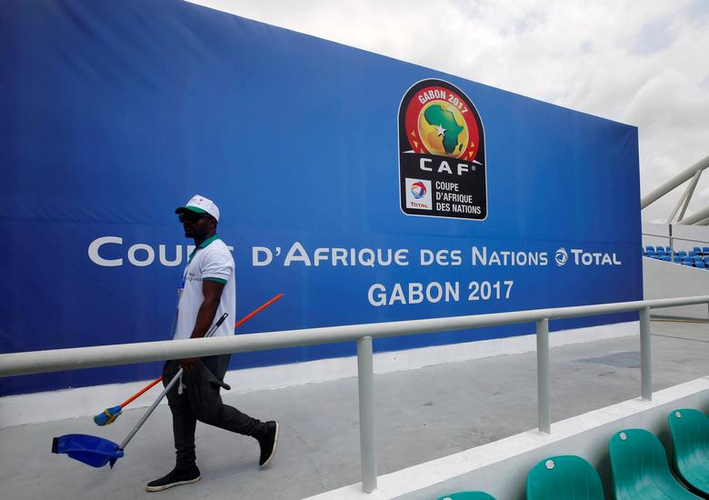 A worker walks past a billboard at the Stade de l'Amitie Sino ahead of the African Nations Cup Soccer Tournament in Libreville, Gabon, January 13, 2017. REUTERS/Mike Hutchings