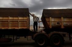 Un camionero brasileño cubre su cara para protegerse del polvo mientras descarga granos en Alto de Araguaia, en Brasil. 24 de septiembre de 2012. Una importante ruta para el transporte de granos en el estado brasileño de Mato Groso, el mayor productor de soja y maíz en el país, fue bloqueada parcialmente el viernes por conductores de camiones que exigen un mayor sueldo en momentos en que comienza la cosecha, dijeron policías y manifestantes. REUTERS/Nacho Doce