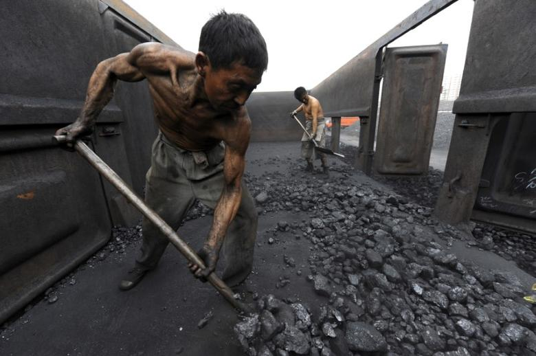 FILE PHOTO: Workers unload coal at a storage site along a railway station in Hefei, Anhui province October 27, 2009.   REUTERS/Jianan Yu/File Photo