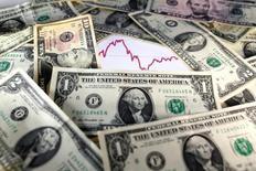 Долларовые купюры на фоне графика. 7 ноября 2016 года. Глобальный экономический прогноз остается неустойчивым, несмотря на недавние короткие периоды стабильности, считает подавляющее большинство экономистов, опрошенных Рейтер. Росту, по их мнению, может навредить растущая популярность протекционистской торговой политики. REUTERS/Dado Ruvic/Illustration