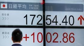 Электронное табло, показывающее динамику индекса Nikkei. Японский индекс Nikkei отскочил от шестинедельного минимума в четверг благодаря финансовому сектору, который оживился после роста доходности американских бондов из-за речи главы ФРС Джанет Йеллен, где она сказала о возможности ускоренного повышения ставок в 2017 году.  REUTERS/Toru Hanai