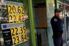 Un policía frente a un cartel que muestra los cambios del peso mexicano fuera de un banco en Ciudad de México.. 11 de enero de 2017. REUTERS/Carlos Jasso