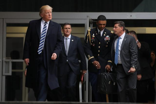 U.S. President Donald Trump leaves the Central Intelligence Agency (CIA) headquarters accompanied by National security adviser General Michael Flynn (2nd L)  after delivering remarks during a visit in Langley, Virginia U.S., January 21, 2017. U.S. REUTERS/Carlos Barria