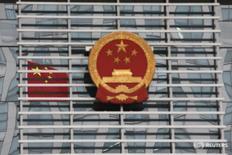Флаг и герб Китая у здания суда в городе Хэфэй 8 августа 2012 года. Предварительный дефицит бюджета Китая в 2016 году составил 2,83 триллиона юаней ($413 миллиардов) - больше, чем целевой показатель 2,18 триллиона юаней, свидетельствуют подсчеты Рейтер, основанные на данных министерства финансов КНР. REUTERS/Aly Song