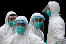 Funcionários usam roupas de proteção em mercado de Hong Kong após descoberta de casos de gripe aviária.     07/06/2016           REUTERS/Bobby Yip