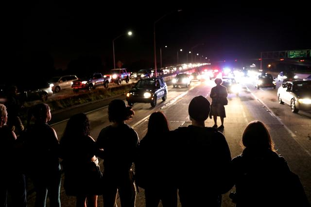 FILE PHOTO --  Demonstrators form a line to stop traffic on Interstate 580 during a demonstration following the election of Donald Trump as President of the United States in Oakland, California, U.S. November 10, 2016. REUTERS/Stephen Lam/File Photo