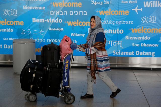 A woman exits immigration after arriving from Dubai on Emirates Flight 203 at John F. Kennedy International Airport in Queens, New York, U.S., January 28, 2017.  REUTERS/Andrew Kelly
