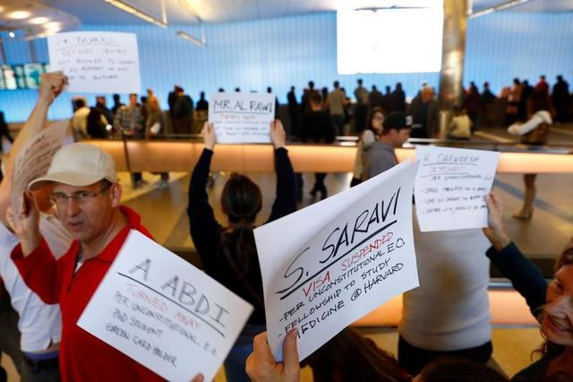 People hold signs with the names of people detained and denied entry in protest of Donald Trump's travel ban at Los Angeles International Airport (LAX) in Los Angeles, California, U.S., January 28, 2017.  REUTERS/Patrick T. Fallon - RTSXU2Q