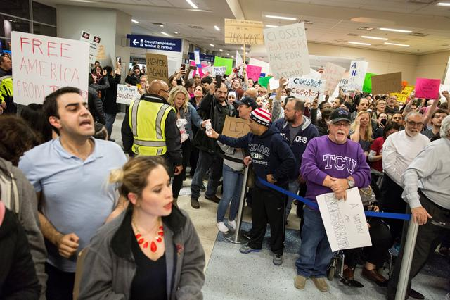 People gather at an international arrival gate to protest against the travel ban imposed by U.S. President Donald Trump's executive order, at Dallas/Fort Worth International Airport in Dallas, Texas, U.S. January 28, 2017.  REUTERS/Laura Buckman