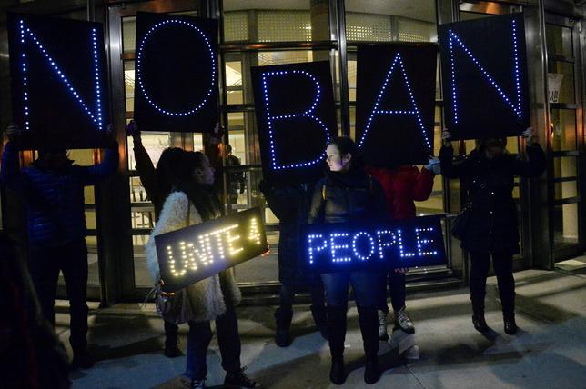 1月29日、米カリフォルニア、ニューヨークなど14州と首都ワシントンの司法長官は、イスラム圏7カ国の市民の入国禁止などを決めた米大統領令を非難する共同声明を出した。写真は同大統領令に抗議する人々。ニューヨークで28日撮影(2017年 ロイター/Rashid Umar Abbasi)