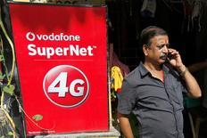 Vodafone dijo el lunes que estaba en conversaciones para fusionar sus operaciones en India con las de su rival Idea Cellular, en una operación en acciones que podría ayudar a ambos grupos a contrarrestar la dura competencia en este mercado asiático. En la imagen de archivo, un hombre habla con su móvil ante un anuncio de Vodafone en Kolkata, India, el 26 de septiembre de 2016. REUTERS/Rupak De Chowdhuri
