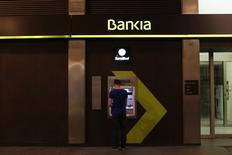 Bankia anunció el lunes un descenso del 22,7 por ciento en el beneficio atribuido de 2016, presionado por el  deterioro del margen de intereses y nuevas provisiones relacionadas con las cláusulas suelo en las hipotecas vendidas a a sus clientes. En la imagen, un hombre utiliza un cajero de Bankia en Sevilla, 4 de marzo de 2016. REUTERS/Marcelo del Pozo